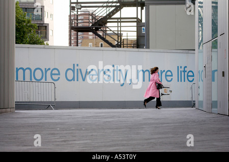 MORE DIVERSITY, MORE LIFE and a walking woman, London, Great Britain - Stock Photo