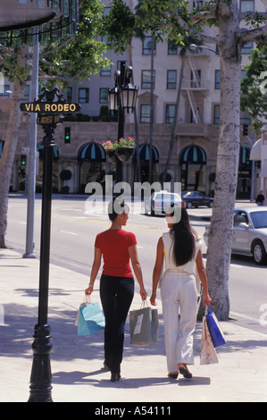 Two women with shopping bags on Rodeo Drive in Beverly Hills California - Stock Photo