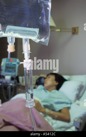 Woman connected by IVs to fluids in hospital recovery room bed - Stock Photo