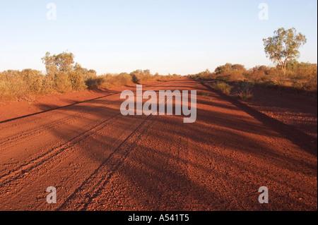 Straight gravel road in Pilbara outback at sunset western australia WA - Stock Photo