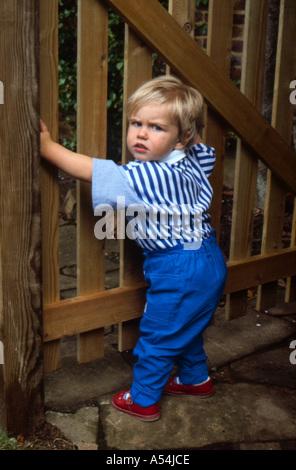 Toddler opening gate - Stock Photo