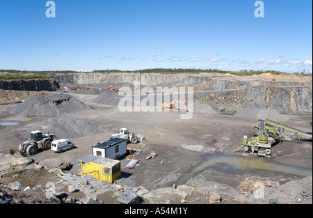 Machinery and and site huts at the bottom of a rock quarry , Finland - Stock Photo