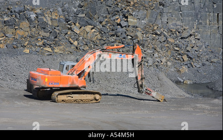 An orange excavator at the bottom of a rock quarry equipped with rock hammer , Finland - Stock Photo