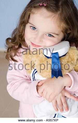 Girl hugging teddy bear - Stock Photo