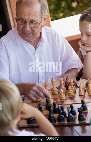 Grandfather playing chess with grandchildren - Stock Photo