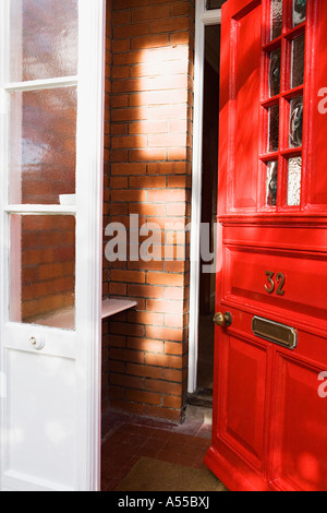 Red painted front door window and flower display in barrow outside