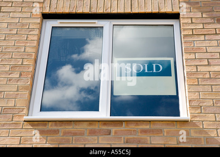 Sold sign in window of new house - Stock Photo