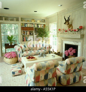 Pale Ikat-style patterned sofas and armchairs beside fireplace in white eighties living room with baskets of pink - Stock Photo