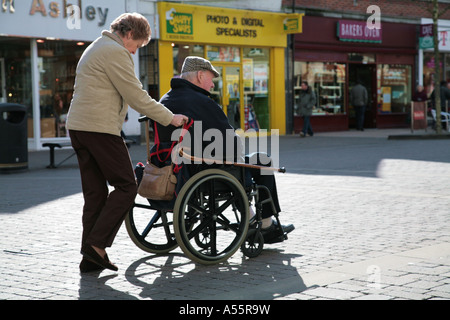 man in wheelchair in shopping centre - Stock Photo