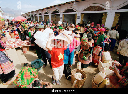 A Vietnamese boy carries plastic containers used in sale of homemade liquor at the market in BacHa Northern Vietnam - Stock Photo