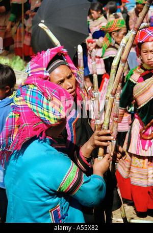 Hmong women buy sugarcane at the market in BacHa Northern Vietnam - Stock Photo