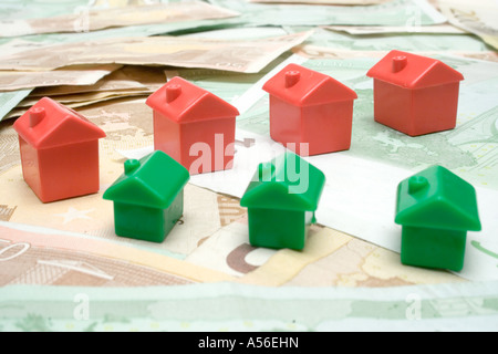 Red and green plastic houses standing on Euro banknotes. - Stock Photo