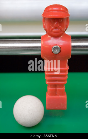 Tabletop football. Red striker dribbles with the ball. - Stock Photo