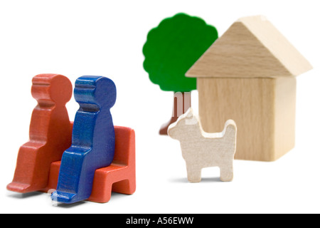 Couple with dog sitting in front of their home. Playthings isolated on a white background. - Stock Photo