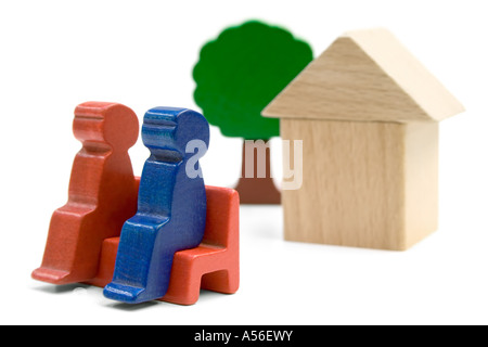 Couple sitting in front of their home. Playthings isolated on a white background. - Stock Photo