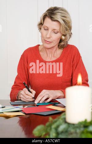 Woman writing Christmas cards - Stock Photo