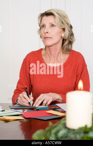 Woman writing Christmas cards, looking away, portrait - Stock Photo