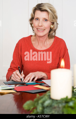 Woman writing Christmas cards, smiling, portrait - Stock Photo