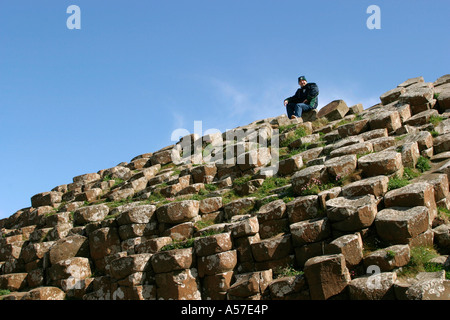 County Antrim Giants Causeway man sat on rocks - Stock Photo
