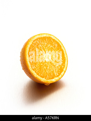 A juicy fresh Orange cut in half - Stock Photo
