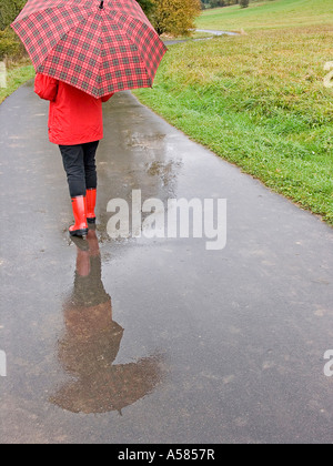 Woman with an umbrella going for a walk on a wet field track in autumn - Stock Photo