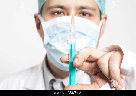 Surgeon with a syringe - Stock Photo