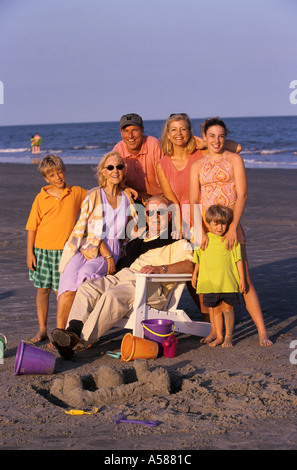 Portrait of an extended family joined together at the beach including parents grandparents and children - Stock Photo
