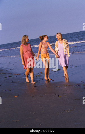 Grandmother mother and daughter holding hands while strolling along the beach shore - Stock Photo