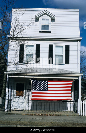 Three story white frame house with large American flag hanging on front porch - Stock Photo