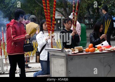 Women pray with  huge ceremonial joss sticks at the monastery at the Tian Tan  Buddha, Lantau Island,  Hong Kong - Stock Photo