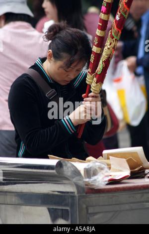 Woman prays with a huge ceremonial joss stick  at the monastery at the Tian Tan Buddha, Lantau Island,   Hong Kong - Stock Photo