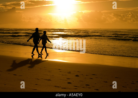 Silhouette of couple strolling along the beach - Stock Photo