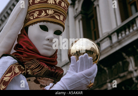 Woman wearing mask and dressed-up in fancy costume holding orb during Venetian Carnival, Venice, Italy - Stock Photo
