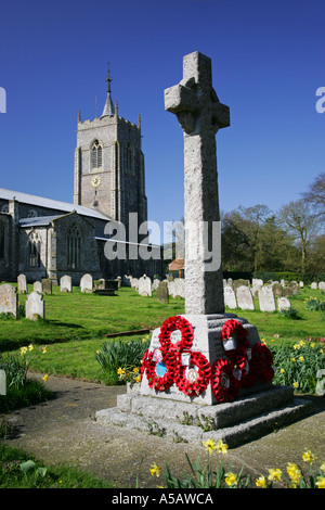 War memorial with red remembrance poppies in a typical lush green English British churchyard Norfolk UK - Stock Photo