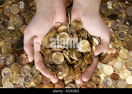 Female hands grabbing shiny coins. - Stock Photo