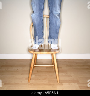 Man standing on chair to reach something high - Stock Photo