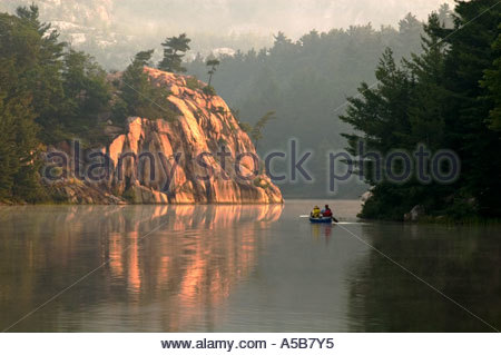 George Lake at dawn with canoeists. Killarney Provincial Park Ontario - Stock Photo