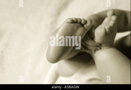 B&W detail of baby's feet and hands. - Stock Photo