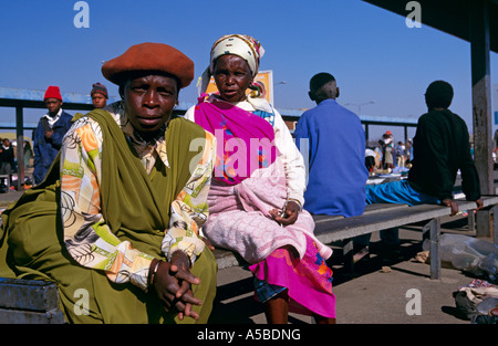 Villagers waiting on bench, Soweto, South Africa - Stock Photo