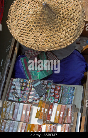 Spice packet seller in conical straw hat Damnoen Saduak floating market Thailand - Stock Photo