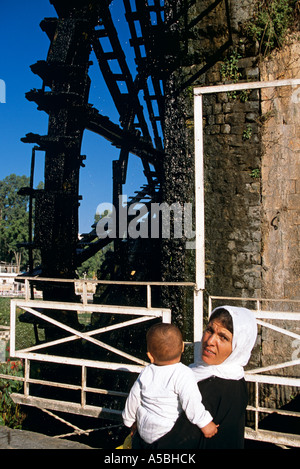 A woman with her baby and the Hama water wheel in the background - Stock Photo