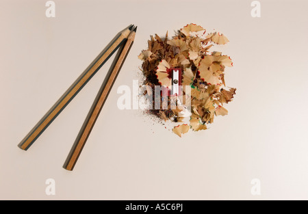 Red pencil sharpener with two coloured pencils and shavings on white table background - Stock Photo