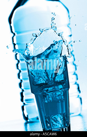 Splashing glas of water in front of a bottle - Stock Photo