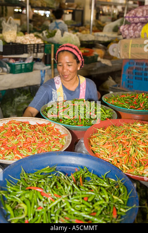 Woman selling Bowls of Various Chillies at Asian Indoor Food Market  in Krabi Province, Thailand - Stock Photo