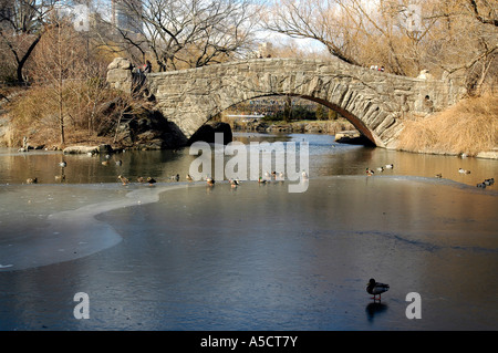 Gapstow Bridge over the frozen Central Park Pond in the winter - Stock Photo