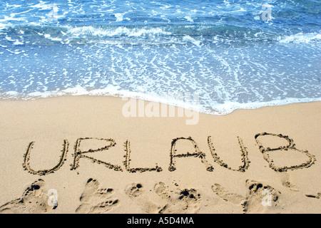 Word (Vacation) written in sand on beach - Stock Photo