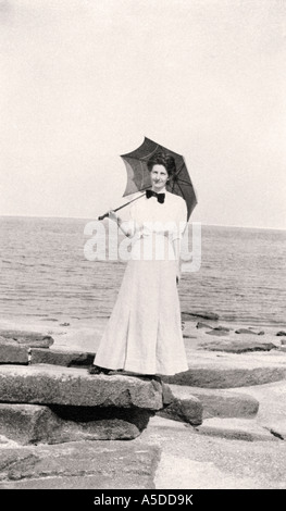 Historic photograph of Victorian woman on beach with umbrella - Stock Photo