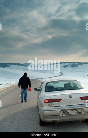 Man Starts the Long Walk Along an Isolated Country Road in Winter to Find Fuel for His Broken Down Car