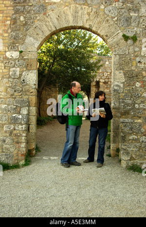 San Gimignano Tuscany Italy couple reading a guide books in archway in vertical - Stock Photo
