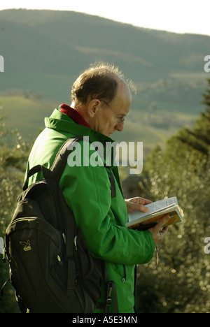 Backlit man in green jacket glasses backpack reads guidebook against the landscape of Tuscany Italy Rough Guide - Stock Photo